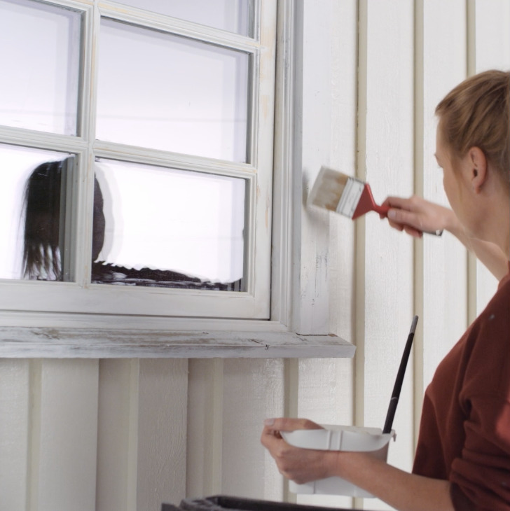 Kvinne maler vindu utendørs