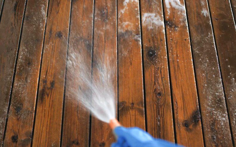 Vasking av gammel treterrasse med hageslange