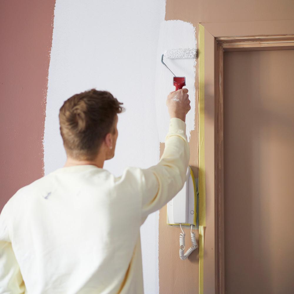 Maling rundt inngangsdøren med en malerull
