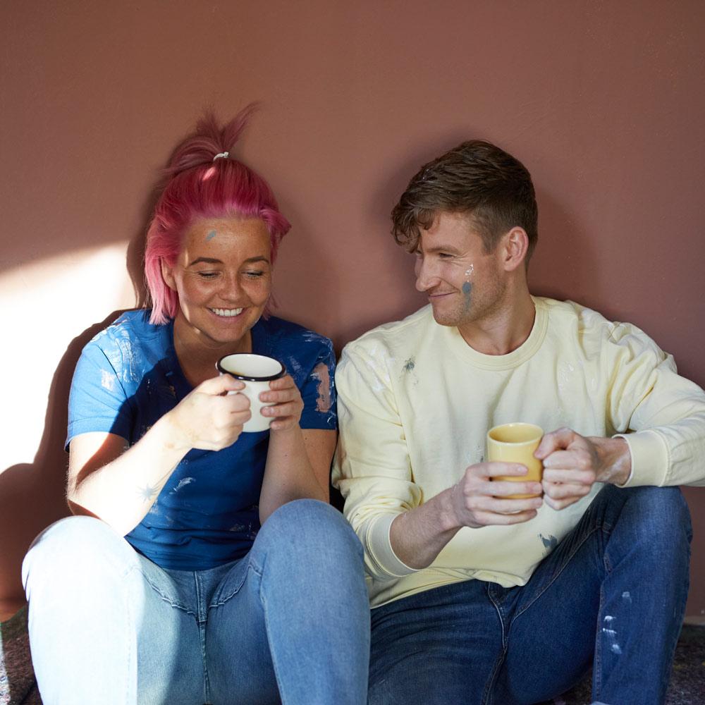 To personer som tar seg en pause fra malingen og nyter en kopp kaffe